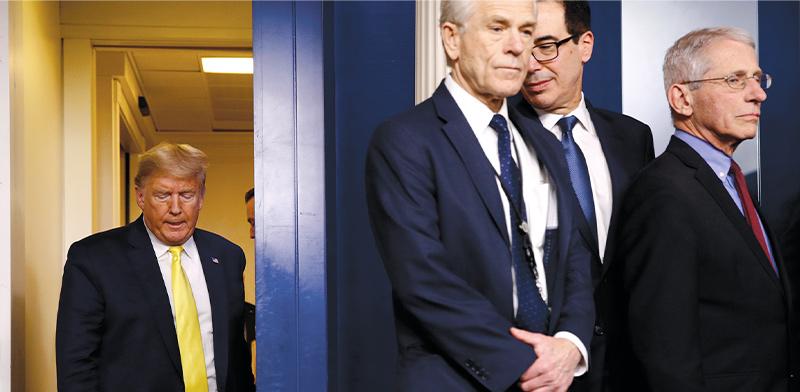 """טראמפ מגיע למסיבת עיתונאים שעסקה בקורונה והשווקים. מימין: ד""""ר אנתוני פאוצ'י, ראש המכון האמריקאי לאלרגיות ומחלות מדבקות, סטיב מנוצ'ין שר האוצר ופיטר נבארו, היועץ של טראמפ לענייני סחר / צילום: Patrick Semansky, AP"""