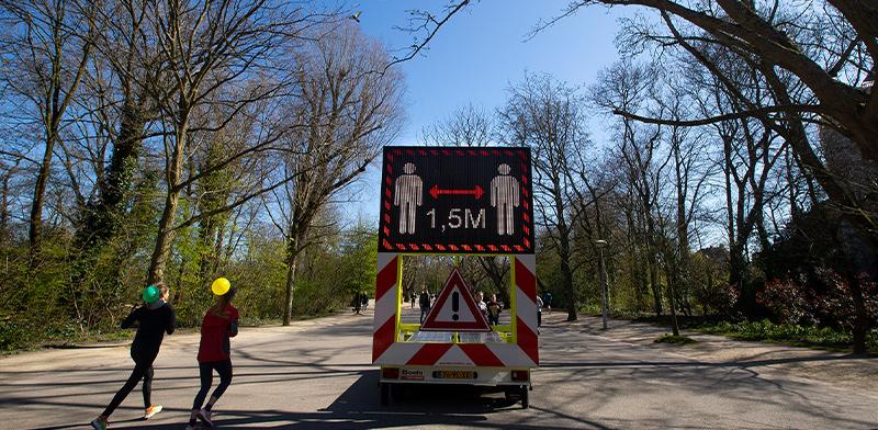 שלט הסברה בפארק בהולנד על שמירת המרחק ההכרחי בין אדם לאדם / צילום: Peter Dejong, Associated Press