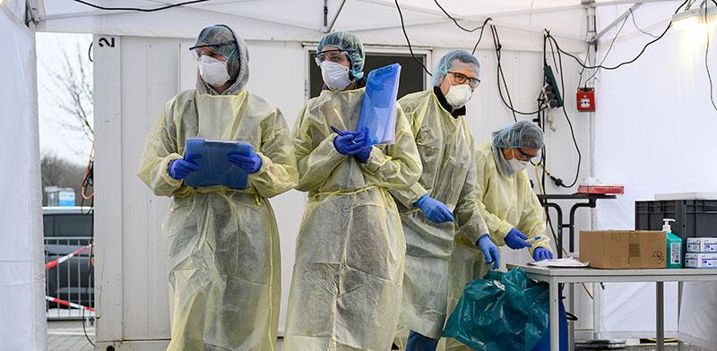 עובדי מעבדה מבצעים בדיקות קורונה בשטוטגרט, החודש / צילום: Sebastian Gollnow, Associated Press