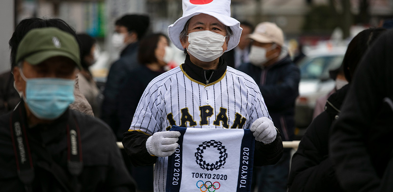 הסמל האולימפי מודפס על דגל מאולתר של אחד הצופים בלהבה האולימפית בפוקושימה, יפן / צילום: Jae C. Hong, Associated Press