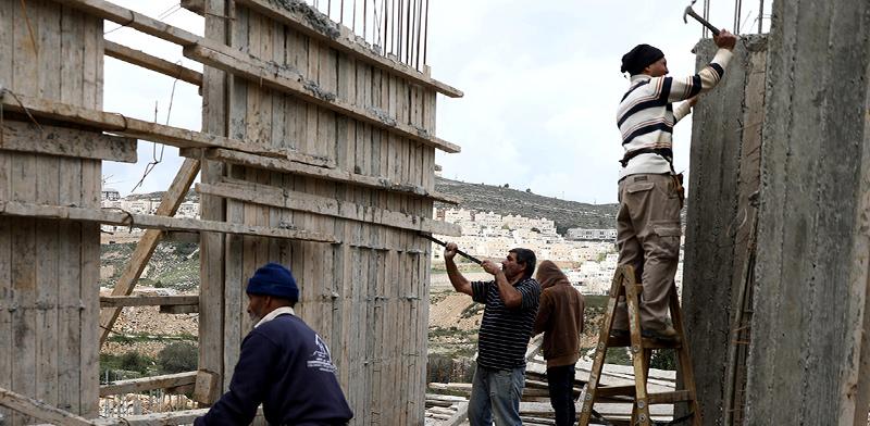 פועלים פלסטינים באתר בנייה / צילום: Ammar Awad, רויטרס