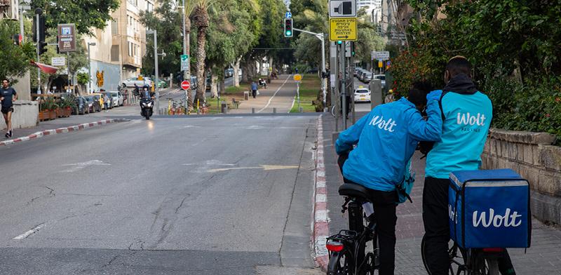 """שליחים של חברת המשלוחים """"וולט"""" משקיפים לעבר רחוב ריק בצל הקורונה / צילום: כדיה לוי, גלובס"""