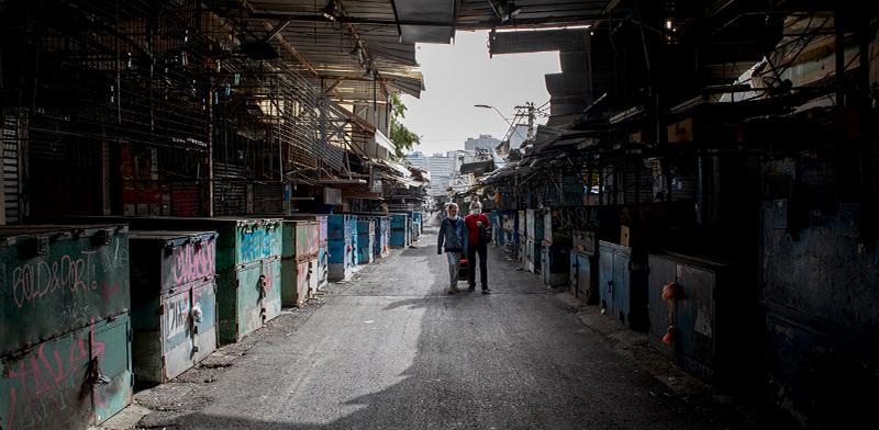 שני עוברי אורח, מצוידים במסיכות מגן, חולפים על פני דוכנים סגורים בשוק / צילום: כדיה לוי, גלובס