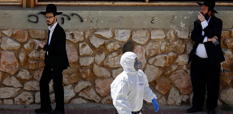 פקח משטרתי עובר בשכונה בבני ברק בחליפת מגן / צילום: Ariel Schalit, Associated Press