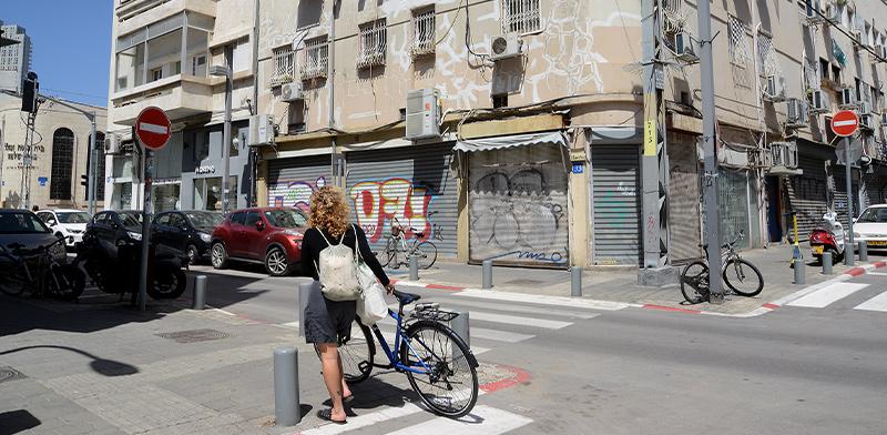 צעירה עם אופניים משקיפה על הרחוב הריק, דרום תל אביב. מאז התפשטות הקורונה משרד הבריאות הורה על סגירת מרבית העסקים במדינה / צילום: איל יצהר, גלובס