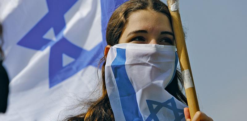 מפגינה ליד משכן הכנסת בירושלים בחודש שעבר, במחאה על מדיניות הממשלה במשבר הקורונה  / צילום: Sebastian Scheiner, Associated Press