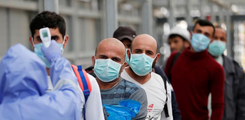 פועלים נבדקים בכניסה לרשות הפלסטינית / צילום: Mussa Qawasma, רויטרס