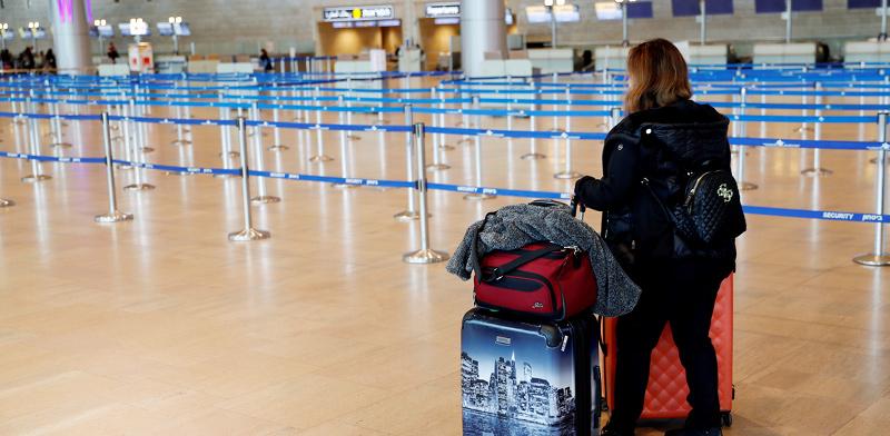 """נוסעת חוזרת לשדה תעופה ריק בצל הקורונה. כ־75 אלף איש נחתו בנתב""""ג מאז המשבר לאחר שהות ממושכת בחו""""ל / צילום: רויטרס"""