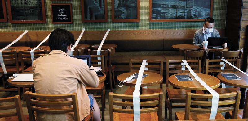 סניף סטארבקס בהונג קונג. המקומות שלא ניתן לשבת בהם סומנו בסרטים / צילום: רויטרס, Tyrone Siu