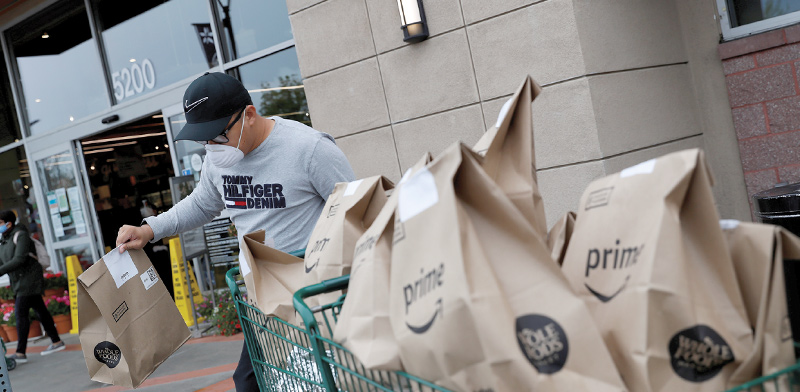 שליח של אמזון מפיץ סחורה בימי מגפת הקורונה / צילום: SHANNON STAPLETON, רויטרס