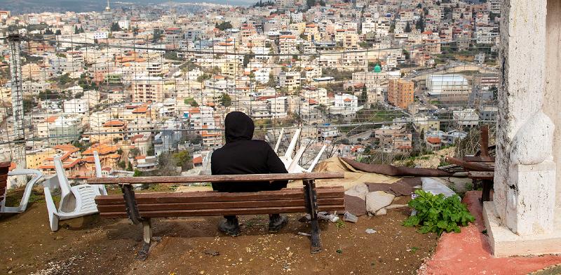 צעיר ערבי-ישראלי צופה על הישוב הערבי אום אל פאחם. כ–50% מהמשפחות הערביות נמצאות מתחת לקו העוני והתלמידים הערבים מופלים בתקציבים גם במערכת החינוך כולה / צילום: Oded Balilty, Associated Press