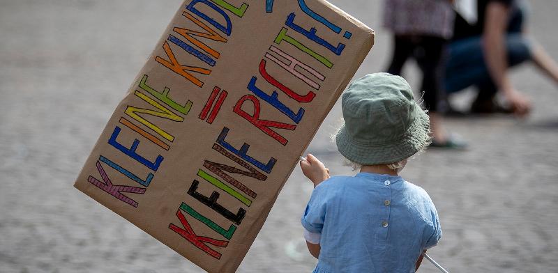 פעוטה מחזיקה שלט במסגרת מחאת הורים על התייחסות המדינה לזכויות ילדים קטנים בתקופת הקורונה / צילום: Michael Probst, Associated Press