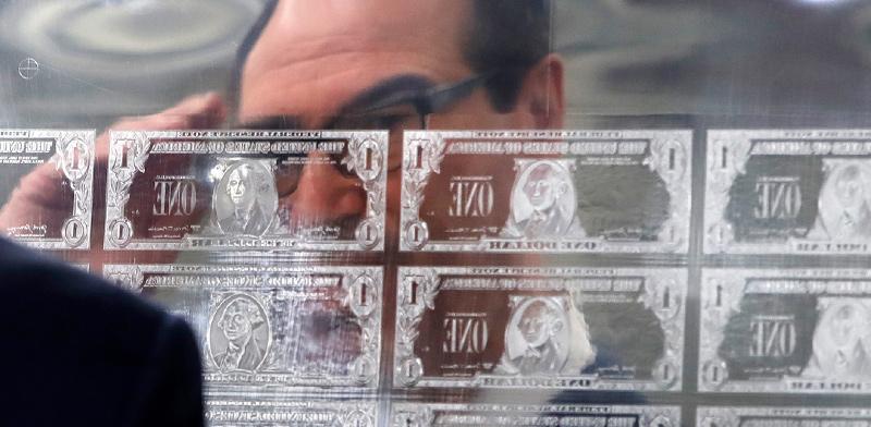 שר האוצר האמריקאי סטיבן מנושין, בוחן גלופה של שטרות דולר במטבעה הלאומית האמריקאית בוושינגטון, 2017 / צילום: Jacquelyn Martin, Associated Press