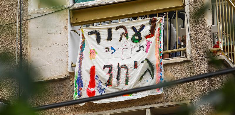 שלט עידוד שנתלה מחוץ לחלון דירה בארץ בצל הסגר / צילום: שלומי יוסף, גלובס