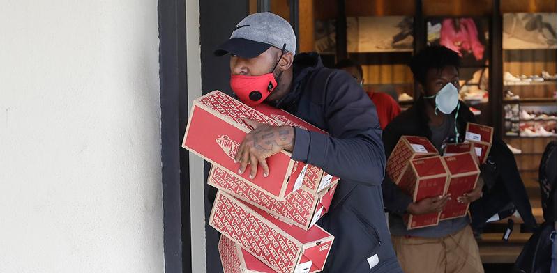 גבר יוצא עם סחורה מחנות VANS בקליפורניה, בראשון / צילום: Marcio Jose Sanchez, Associated Press
