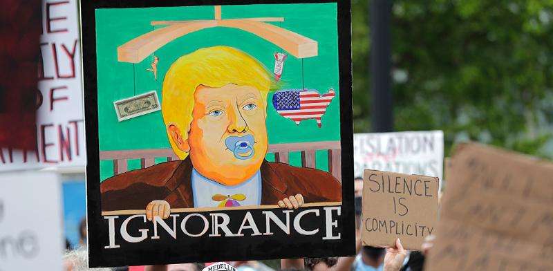 """איור של טראמפ עם הכיתוב """"בורות"""" בהפגנה במיאמי, ביום שבת / צילום: Lynne Sladky, Associated Press"""