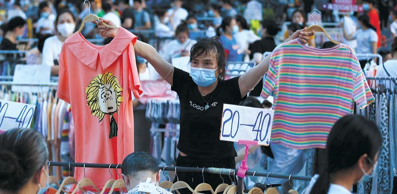 סוחר בדוכני הבגדים בווהאן / צילום: Mark Schiefelbein, Associated Press