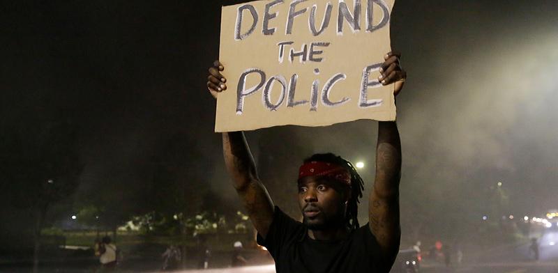 מפגין מול מסעדת וונדי'ס המלאה בעשן לאחר שביום שישי נהרג שם רישרד ברוקס במהלך עימות עם המשטרה / צילום: Brynn Anderson, Associated Press