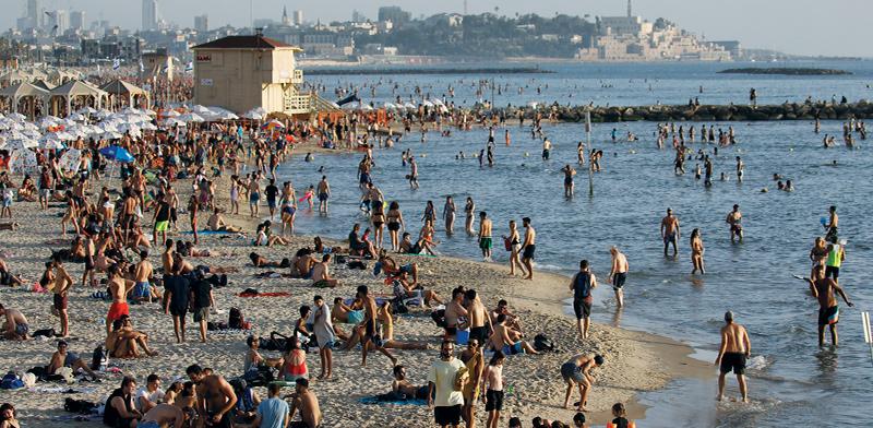 ישראלים מבלים על חוף הים בתל אביב במהלך חודש יוני / צילום: Amir Cohen, רויטרס