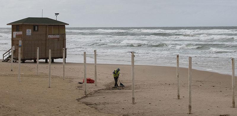 עובד ניקיון בחוף בת ים / צילום: Sebastian Scheiner, Associated Press