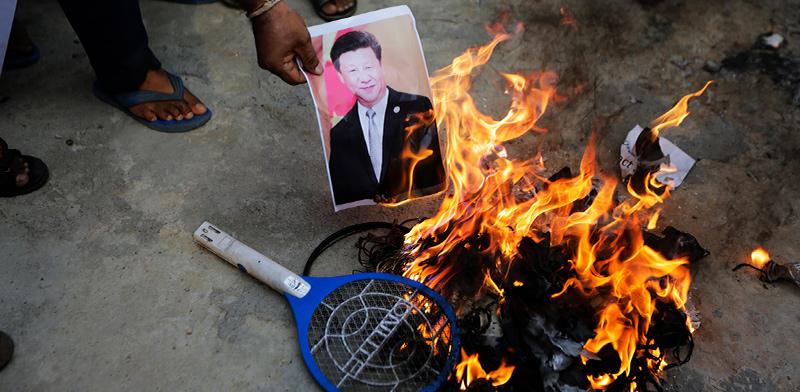 מפגינים הודים שורפים השבוע תמונה של נשיא סין / צילום:  Ajit Solanki, Associated Press