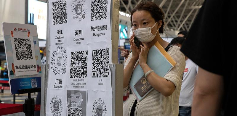 אישה בסין עומדת ליד קיר של קודי בריאות. לכל עיר בסין יש קוד משלה, מה שיצר בעיית תנועה בין הערים / צילום: Ng Han Guan, Associated Press