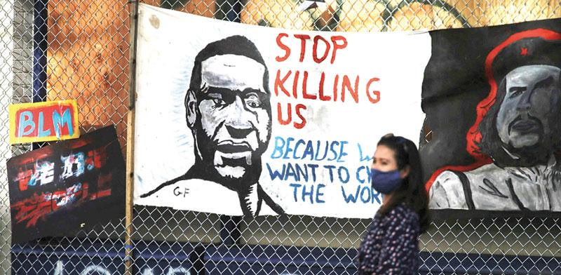 דיוקנו של ג'ורג' פלויד מתנוסס על שלטי המחאה / צילום: LINDSEY WASSON, רויטרס