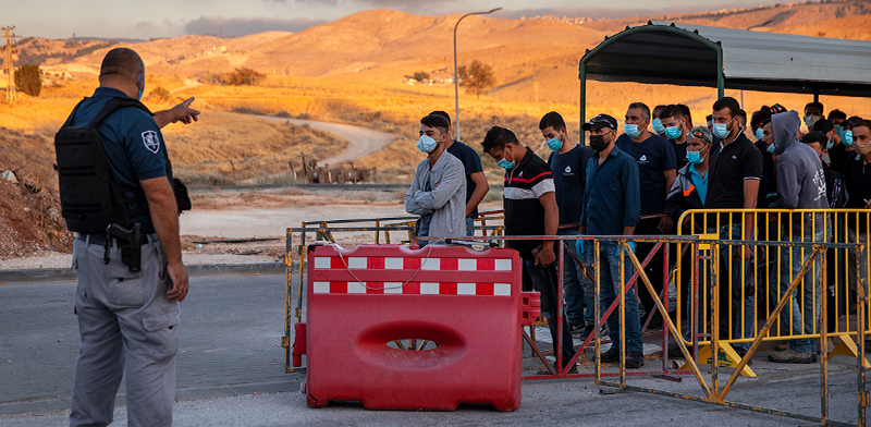 פועלים פלסטינים ממתינים במחסום / צילום: Oded Balilty, Associated Press