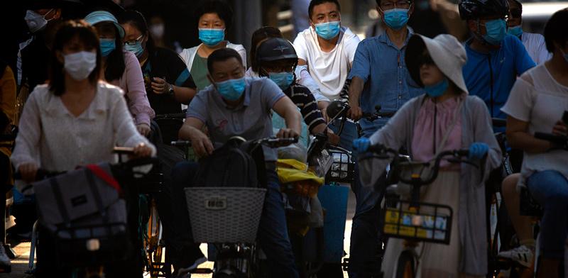 סינים בלב אזור העסקים בבייג'ינג בשבוע שעבר. מצניחה לצמיחה בחצי שנה / צילום: Mark Schiefelbein, Associated Press