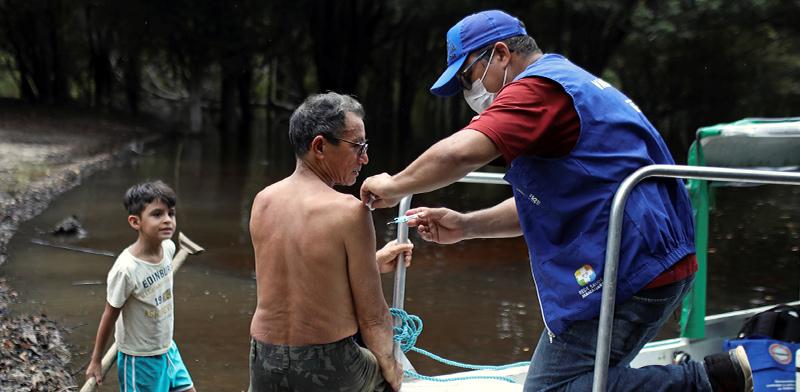 עובד של משרד הבריאות בברזיל מחסן אנשים בשטח נגד שפעת, אפריל / צילום: Bruno Kelly, רויטרס