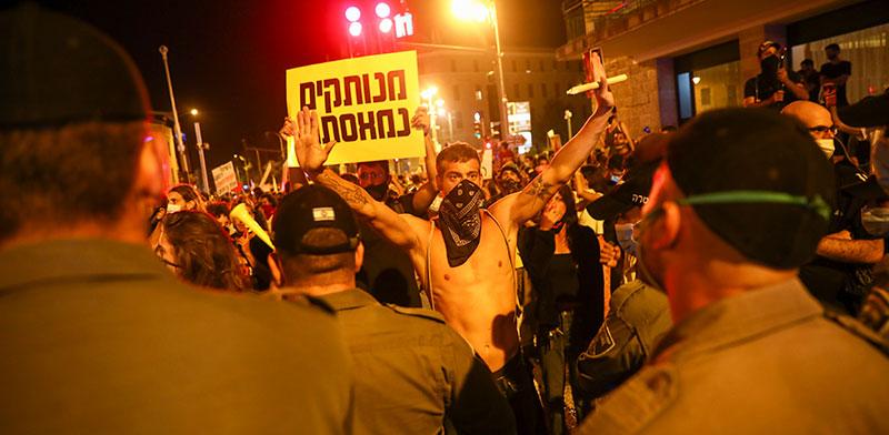 מפגין מסמן עצור בהפגנה בבלפור. האם הוא אנרכיסט? / צילום: Oded Balilty, Associated Press