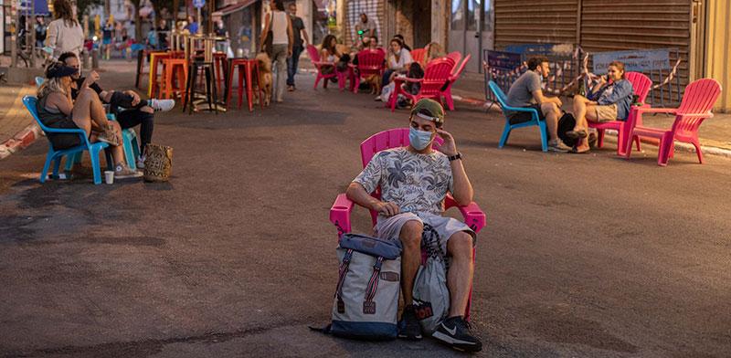 צעיר יושב לבד במדרחוב בתל אביב / צילום: כדיה לוי, גלובס