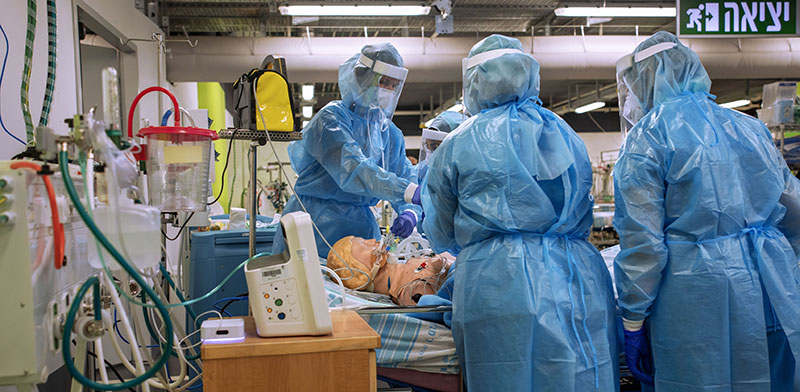 """הצוות הרפואי במחלקת קורונה בבית חולים רמב""""ם מתרגל טיפול בחולה קורונה עם מכונת הנשמה. הכניסה לגל השני הצריכה כוננות גבוהה מצד מחלקות הקורונה בישראל / צילום: Oded Balilty, Associated Press"""