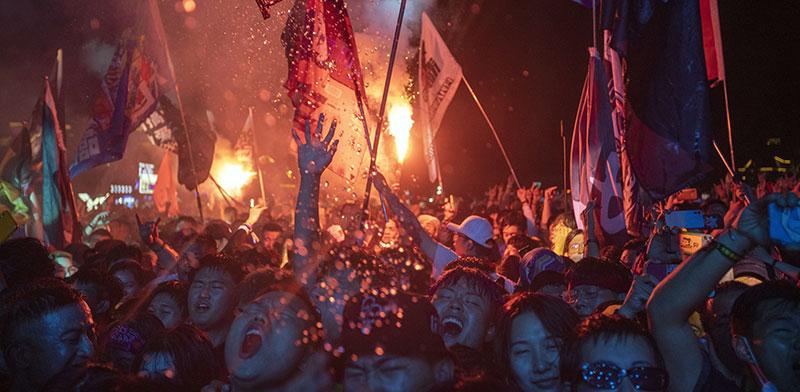 צעירים בפסטיבל מוזיקה במחוז צ'ונגלי בצפון סין. בלי מסיכות ובלי התנצלויות - סין חוגגת ניצחון אסטרטגי במאבק נגד הנגיף / צילום: Ng Han Guan, Associated Press