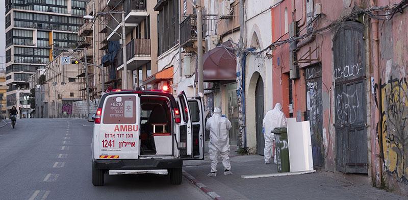 אנשי מגן דוד אדום אוספים אדם החשוד כחולה בקורונה בשבועות הראשונים של התפשטות הוירוס / צילום: Oded Balilty, Associated Press