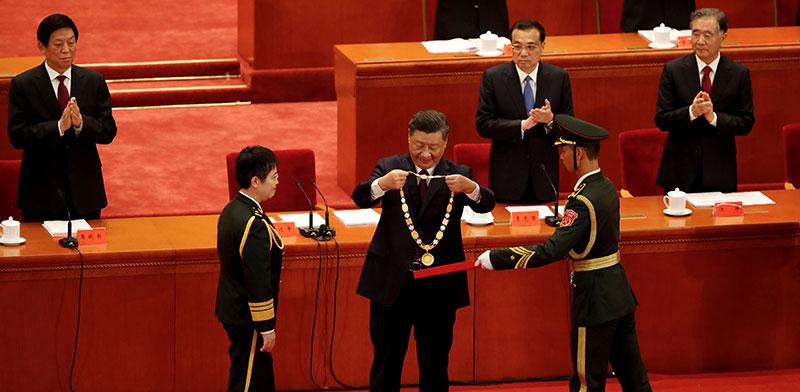 """שי ג'ינפינג מעניק מדלייה לחוקרת החיסונים, הגנרלית צ'ן וויי, בטקס לציון """"מודלים לחיקוי"""", החודש / צילום: רויטרס"""