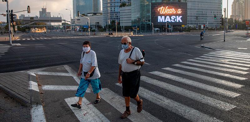 עוברי אורח עם מסכות עוברים שלט על מגדלי עזריאלי שאומר לחבוש מסכה / צילום: Oded Balilty, Associated Press