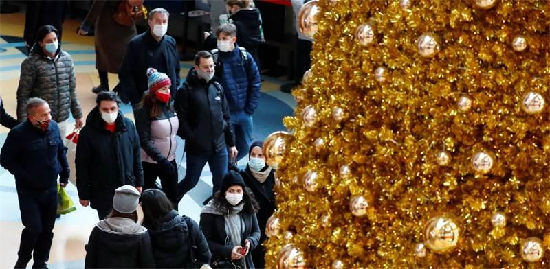 אנשים עם מסכות עובדים ליד עץ חג מולד בברלין / צילום: Fabrizio Bensch, רויטרס