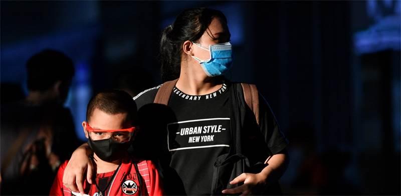 אם ובנה הולכים ברחוב עם מסיכות בצל בהלת הקורונה / צילום: צ'ליני ת'יראסופה, רויטרס