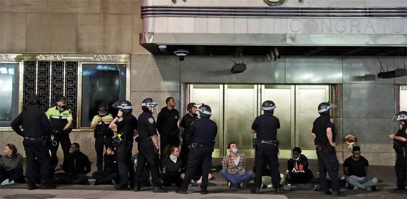 שוטרים עומדים מחוץ לאולם הופעות עם עצורים מההפגנות / צילום: Seth Wenig, AP
