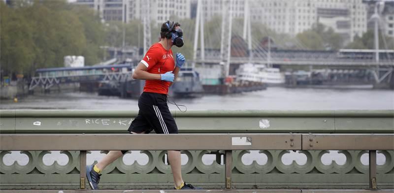 אדם רץ עם מסכה בלונדון, בריטניה / צילום: Kirsty Wigglesworth, AP