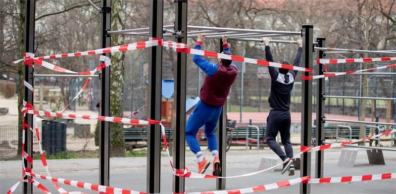 שני גברים מתאמנים בפרק ציבורי בברלין, למרות שהמתקנים נחסמו בעזרת סרטים / צילום: Christoph Soeder, AP