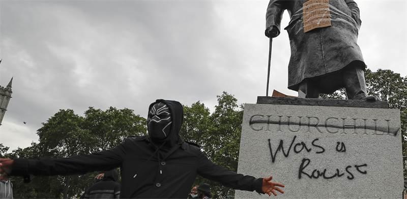 מפגין מול פסל וינסטון צ'רצ'יל שהושחת / צילום: Frank Augstein , Associated Press