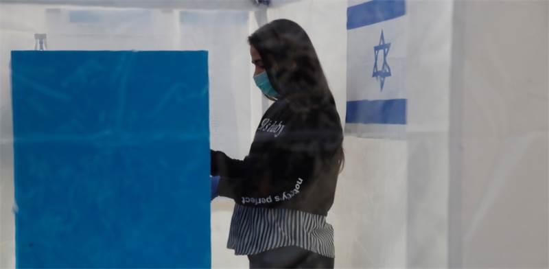 מצביעה בקלפי מיוחד לאנשים שנמצאים בבידוד בשל הקורונה / צילום: Ariel Schalit, AP