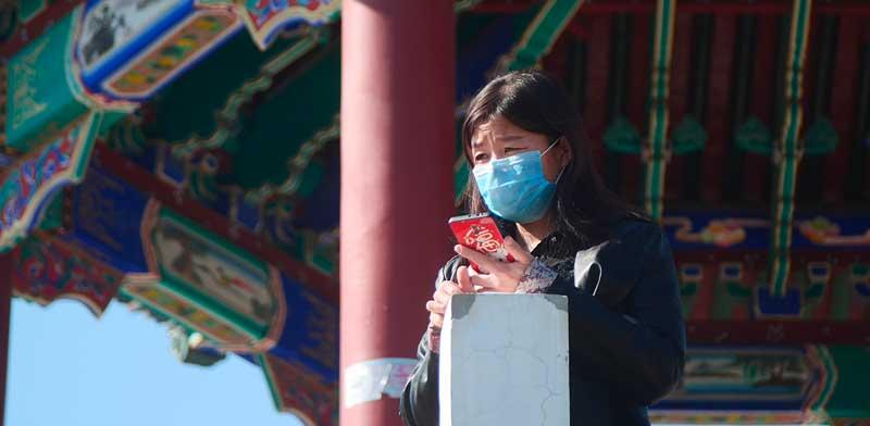 אזרחית בסין מביטה בדאגה / צילום: Sam McNeil AP
