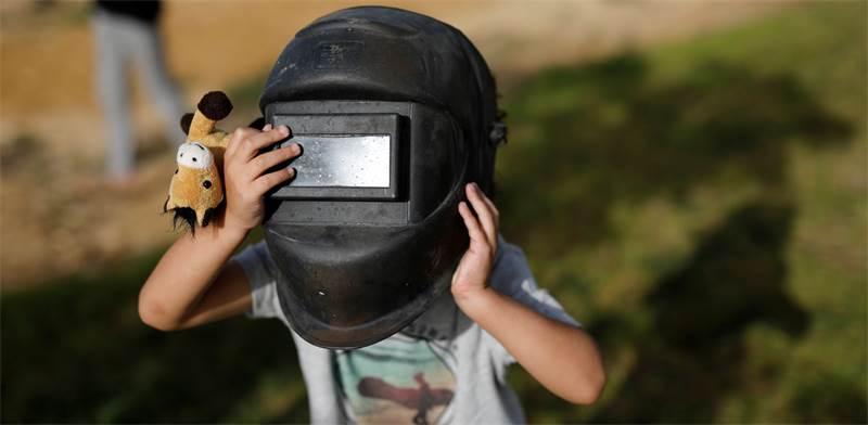 ילד בירוחם צופה בליקוי החמה החלקי. אוסר להביט בליקוי בעיניים חשופות / צילום: Amir Cohen, רויטרס