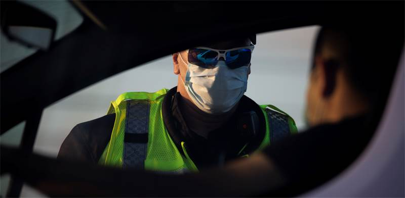 שוטר עם מסיכה מחלק דוח  / צילום: אריאל שליט, AP