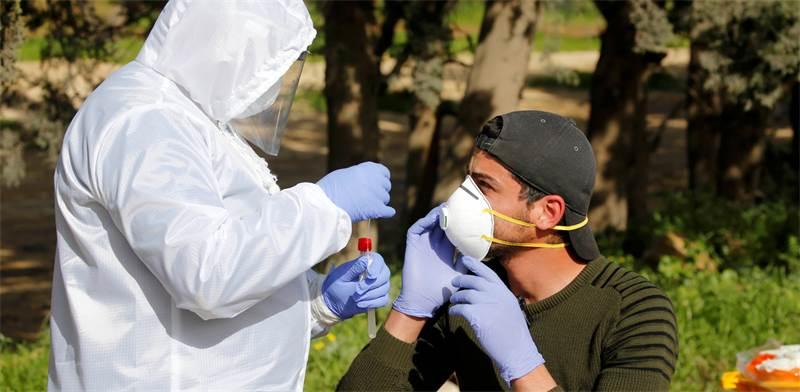 """איש צוות רפואי בודק פועל פלסטיני, שחזר מישראל לשטחי יו""""ש, להימצאות נגיף הקורונה / צילום: Mussa Qawasma, רויטרס"""