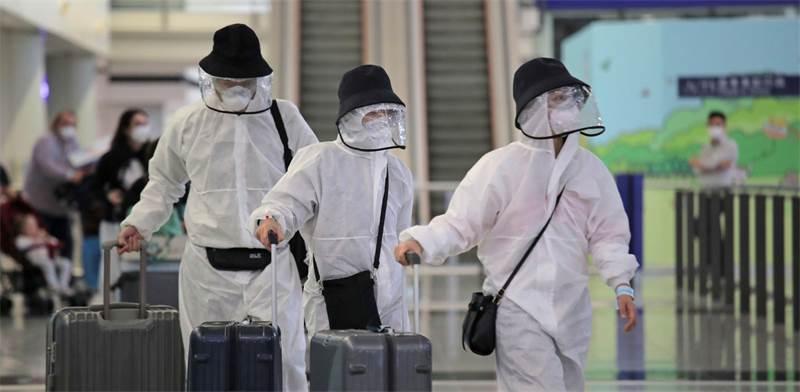 נוסעים לובשים מיגון מפני נגיף הקורונה בשדה התעופה בהונג קונג / צילום: Kin Cheung, AP