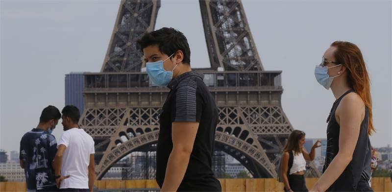 עוברי אורח עם מסכות ליד האייפל בפריז, צרפת / צילום: Michel Euler, AP